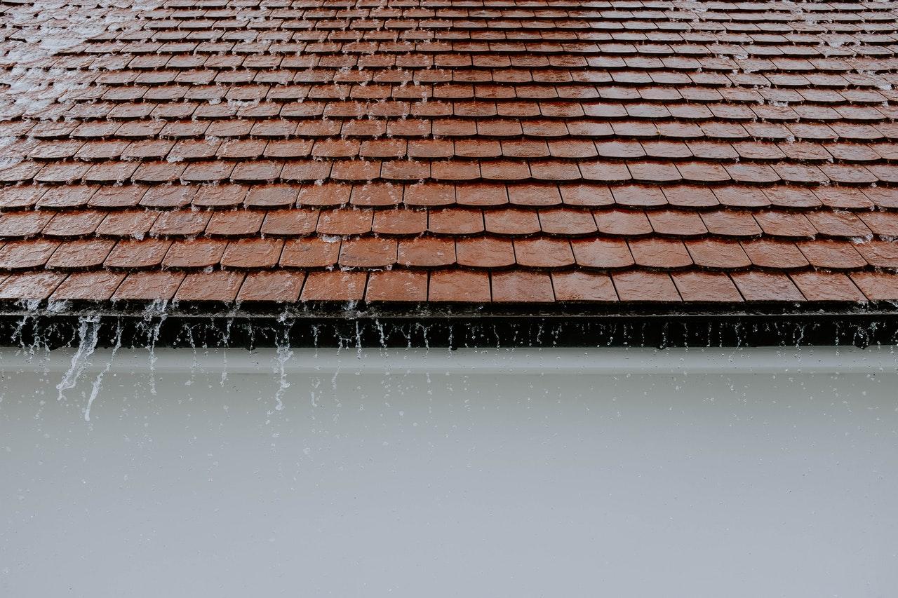 En masse regn løber ned ad tag