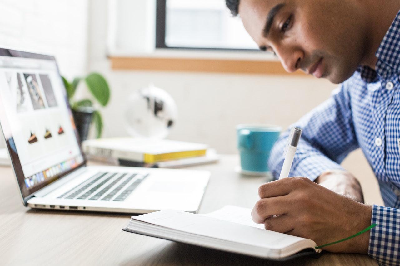 Mand skriver i sine noter på arbejdet