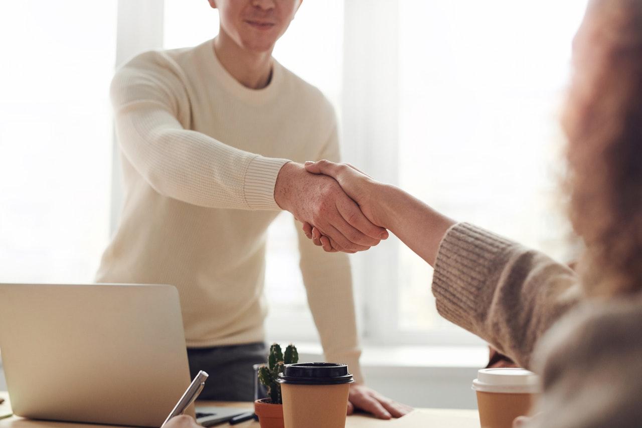 To personer giver hånd til jobsamtale